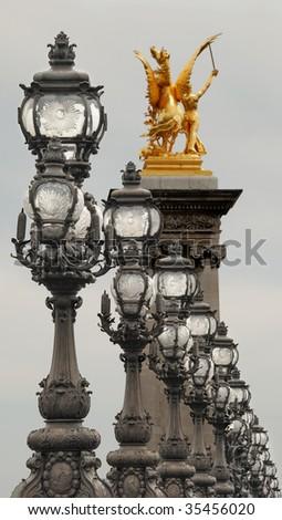 Candlesticks and statue on Bridge Alexander III in Paris, France. - stock photo