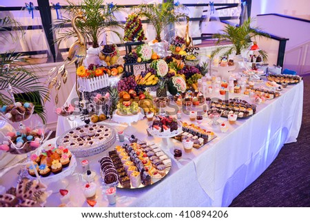 Candy bar with a lot of cookies and fruits during the wedding - stock photo