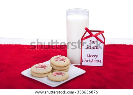 candy cane stripped peppermint flavor sugar cookies on a plate with a glass of milk. Note message tag says for santa merry christmas - stock photo