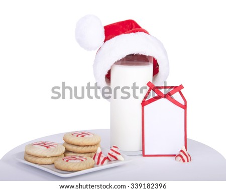 candy cane stripped peppermint flavor sugar cookies on a square plate with a glass of milk wearing a miniature santa hat. Note card next to milk blank for your message - stock photo