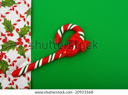 Candy cane with leaves and holly berries on green background, Christmas background