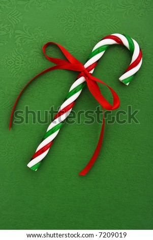 Candy cane with red ribbon on green background