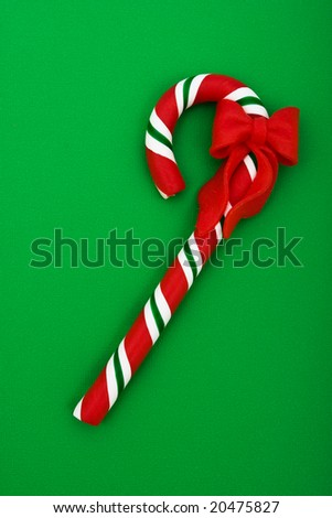 Candy cane with red ribbon on green background, Christmas background
