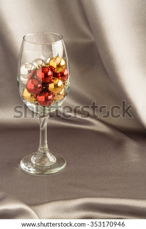 Candy canes in a clear wineglass on a silver background