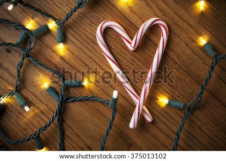 Candy Canes Making a Heart and White Christmas Lights - stock photo