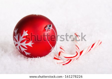 Candy canes with red Christmas ball ornament on snow background