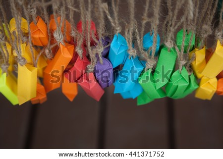 Candy colored paper wrappers hanging on the ropes. Chocolates in the form of a rainbow. Background brown board. Jute rope.