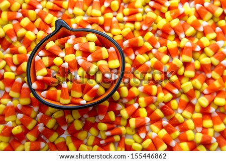 Candy corn candies in orange pumpkin bowl - stock photo