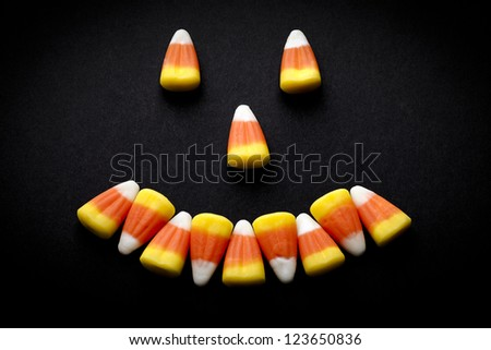 Candy corn forming a happy face. - stock photo