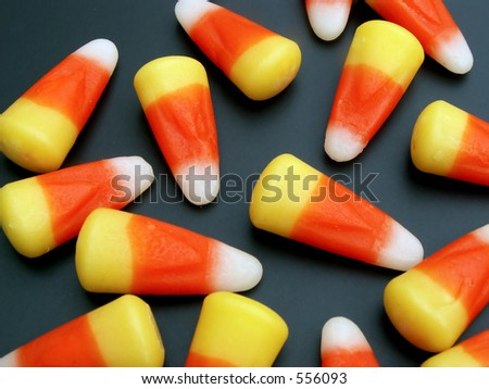 candy corn scattered on black background - stock photo
