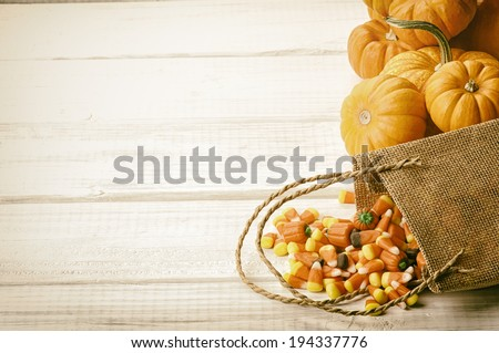 Candy Corn Spilling from Burlap Bag on Rustic White Wood Board Background with room or space for copy, text.   Horizontal, vintage sepia processing  - stock photo