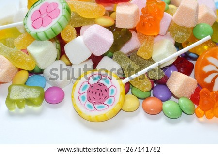 Candy, lollipop, colored smarties and gummy bears on white background - stock photo