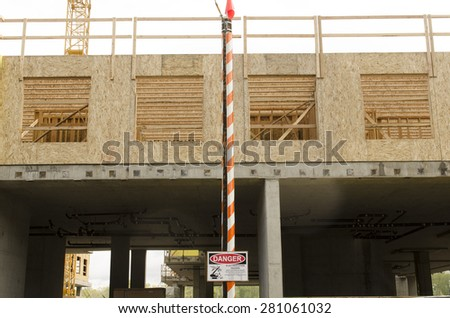 Candy striped pole holds up and warns of high voltage power lines above at a construciton site - stock photo