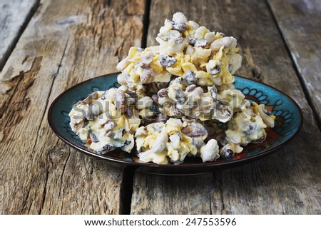 candy with nuts and raisins in white chocolate on a wooden background. oriental sweets. selective focus - stock photo