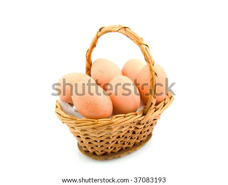 Cane basket filled with chicken eggs isolated on white background - stock photo