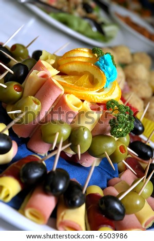 Cannapes decorated with olives and orange. - stock photo