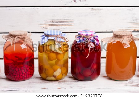 Canned compotes in large glass jars. Summer fruit drinks in glass jars. - stock photo