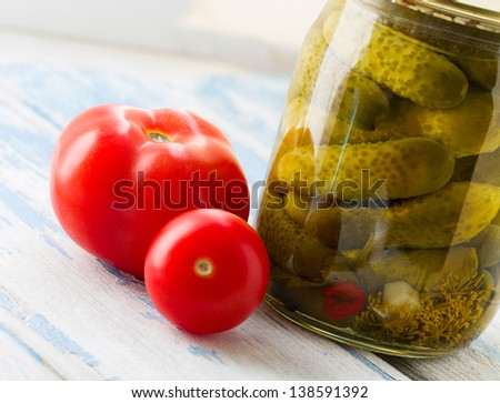Canned cucumbers and tomatoes on wood table close-up