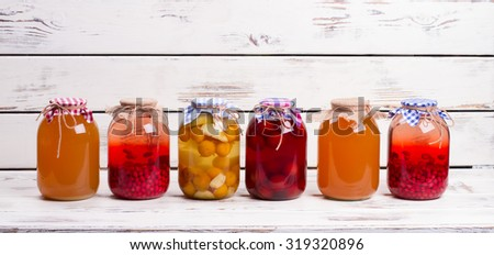 Canned fruit drinks in glass jars. Natural juices are on old wooden shelf. - stock photo