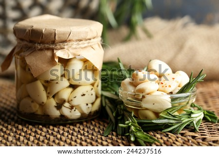 Canned garlic in glass jar and wicker mat and rosemary branches, on wooden background - stock photo