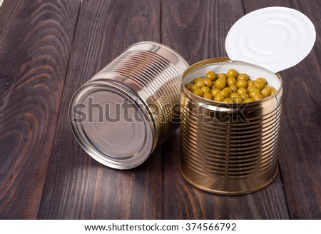 canned green peas in a bank on wooden table. - stock photo