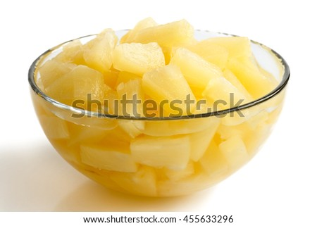 Canned pineapple pieces in a glass bowl isolated on white.