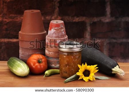 canned relish in a garden set with brick background - stock photo