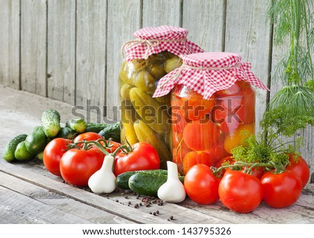 canned tomatoes and pickled cucumbers, homemade preserved vegetables - stock photo