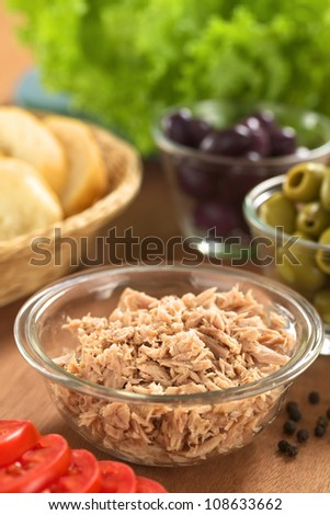 Canned tuna in glass bowl with fresh salad ingredients (olives, tomato, lettuce) and bread (Selective Focus, Focus one third into the tuna)