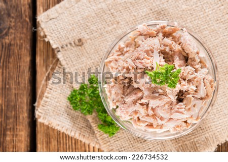 Canned tuna with fresh parsley (detailed close-up shot) on wooden background - stock photo