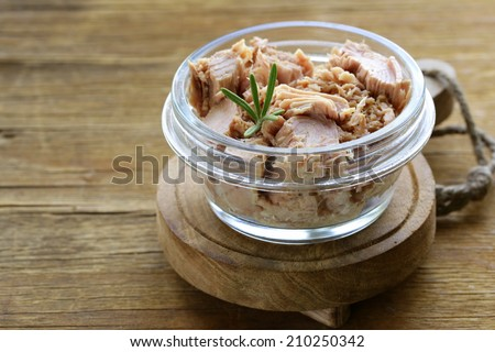 canned tuna with rosemary in a glass jar - stock photo