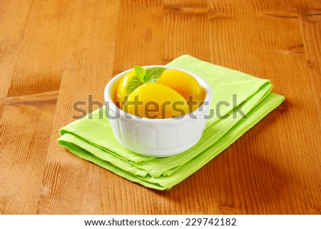 Canned yellow peach in porcelain bowl - stock photo