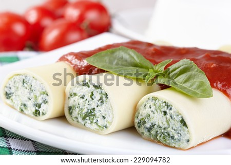 Cannelloni with spinach and ricotta under tomato sauce - stock photo