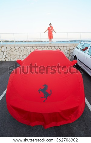 CANNES, FRANCE - JULY 29, 2015: Ferrari red cloth cover at the harbor with woman on July 29, 2015 in Cannes, France. Ferrari emblem is the rampant horse.  - stock photo