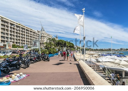 """CANNES, FRANCE - JULY 10, 2014: People walking at embankment near famous """"La Croisette"""" Boulevard. French Riviera. - stock photo"""