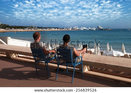 CANNES, FRANCE -  JULY 5, 2014: Two friends relaxing in chairs on Croisette promenade in Cannes, France. CANNES, FRANCE -  JULY 5, 2014: - stock photo