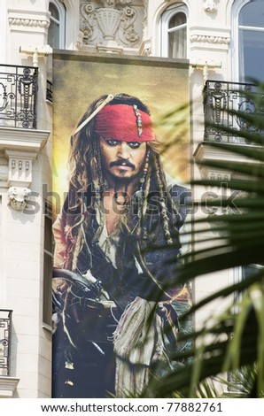 """CANNES, FRANCE - MAY 19: big poster advertise """"the pirates of caribbean series"""" film during the 64th Annual Cannes Film Festival on May 19, 2011 in Cannes, France. - stock photo"""