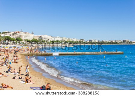 CANNES, FRANCE - SEPTEMBER 13, 2012: Tourists enjoy the good weather at the beach in Cannes, France. The beach and the waterfront avenue, La Croisette, are full almost all the year round - stock photo
