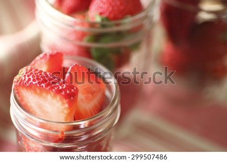 Canning jars with whole and sliced fresh strawberries with copy space - stock photo