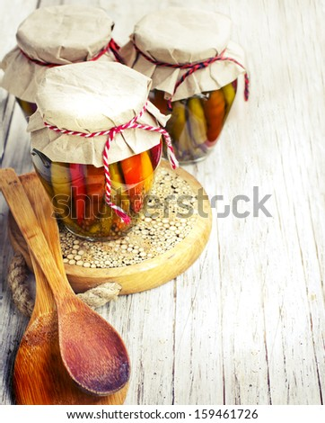 canning vegetables/autumnal background with canned banks on wooden background/preserving the harvest - stock photo