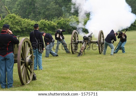 cannon being fired by yankee soldiers in a civil war re-enactment - stock photo