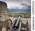 cannon in castle with cloudy sky - stock photo