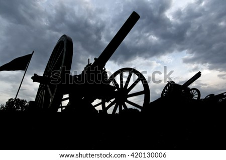 Cannon silhouettes in the late evening. - stock photo