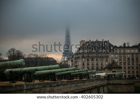 Cannons and the Eiffel Tower in fog