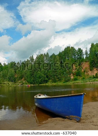 Canoe, river, cliff and trees - stock photo