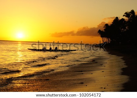 Canoeing during sunset by beach - stock photo