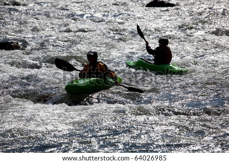 Canoeing in white water in rapids on river - stock photo