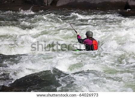 Canoeing in white water in rapids on river with the kayak starting to sink in the waves - stock photo
