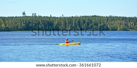 Canoeist at the wild forest lake, called Beauty. Russia, Saint-Petersburg region - stock photo