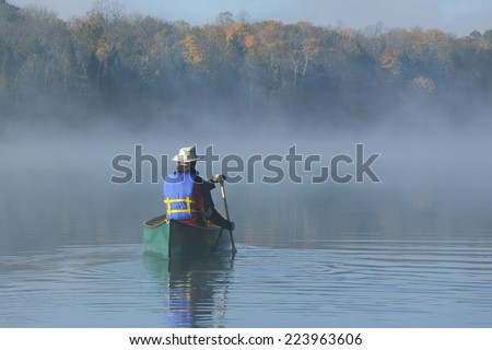 Canoeist Paddling a Green Canoe on a Misty Autumn Lake - Ontario, Canada - stock photo